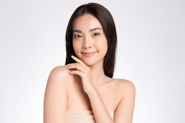 ナチュラルメイク、きれいな肌、白い壁に白い歯を持つ美しい笑顔のアジア女性