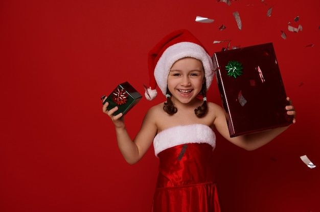 Beautiful smiling baby girl in santa carnival attire, holds christmas gift box in green and red wrapping shiny paper and rejoices posing against colored background with falling sequins and confetti