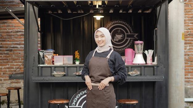 Красивый улыбающийся бариста готов открыть контейнер для будки кафе