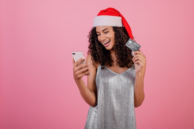 Beautiful smiling black woman with phone and credit card wearing santa hat