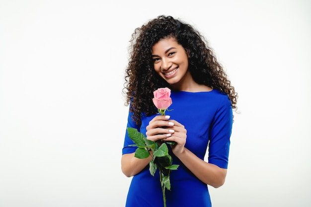 Beautiful smiling black woman with pink rose wearing blue dress