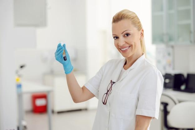 Красивая улыбающаяся блондинка лаборант стоит в лаборатории и держит пробирку с кровью