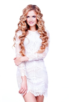 Beautiful smiling blonda girl with long curly hair. full portrait of fashion model posing  on white wall