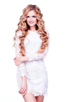 長い巻き毛の美しい笑顔の金髪の女の子。白い壁にポーズをとってファッションモデルの完全な肖像画