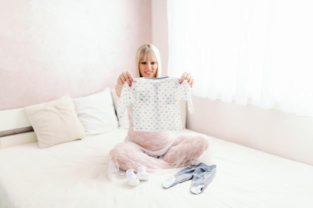 Красивая усмехаясь белокурая кавказская женщина держа и смотря одежды младенца пока сидящ на кровати при пересеченные ноги. интерьер спальни.