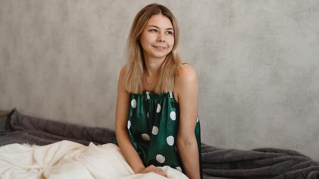 Красивая улыбающаяся блондинка в зеленой пижаме. доброе утро концепция Premium Фотографии