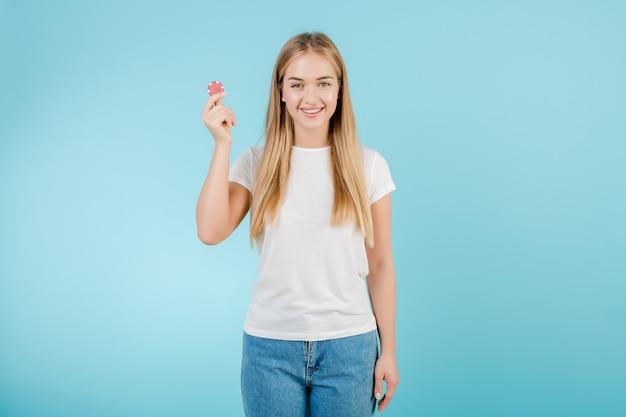 Красивая улыбающаяся белокурая женщина с фишкой для покера из онлайн-казино, изолированная на синем