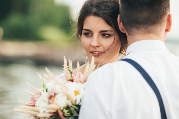 Beautiful smiling bride brunette young woman with boho style bouquet with groom