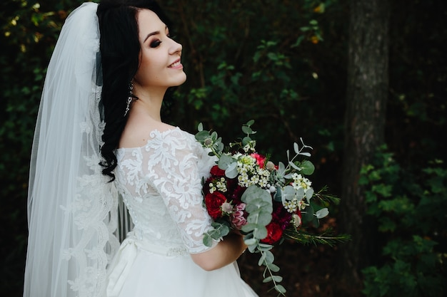 Beautiful smiling bride holding bouquet standing outside