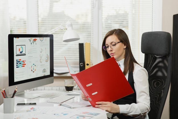 Beautiful smiling brown-hair business woman in black and white suit and glasses sitting at the desk with red folder, mobile phone and cup of coffee, working at computer with documents in light office.