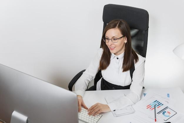 Красивая улыбающаяся каштановая деловая женщина в костюме и очках, сидящая за столом, работающая за компьютером с современным монитором с документами в легком офисе, руки на клавиатуре