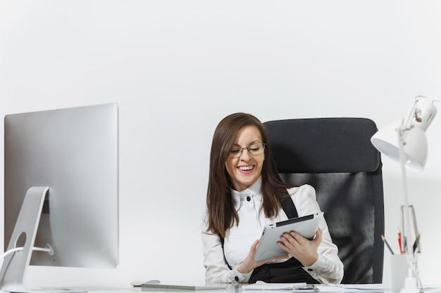 Красивая улыбающаяся каштановая деловая женщина в костюме и очках сидит за столом, работая за компьютером с современным монитором с документами и планшетом в легком офисе
