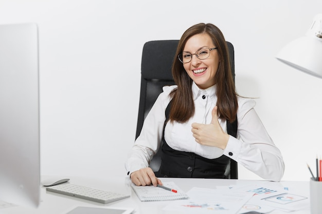 책상에 앉아 안경을 쓰고 웃고 있는 아름다운 갈색 머리 비즈니스 여성, 밝은 사무실에 있는 문서가 있는 현대적인 모니터로 컴퓨터 작업, 엄지손가락을 보여주는