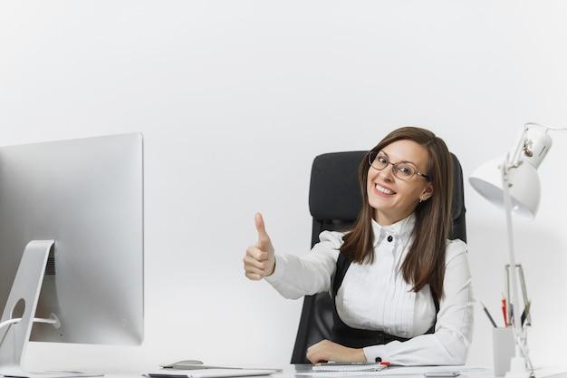 Красивая улыбающаяся каштановая деловая женщина в костюме и очках, сидящая за столом, работающая за компьютером с современным монитором с документами в светлом офисе, показывая большой палец вверх