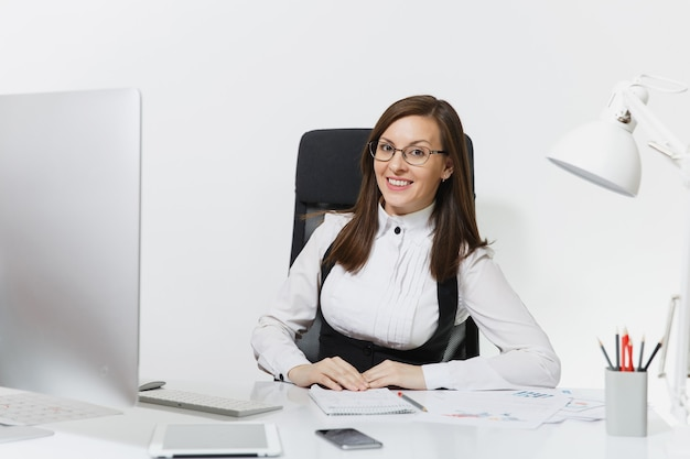 책상에 앉아 안경을 쓰고 웃고 있는 아름다운 갈색 머리 비즈니스 여성, 밝은 사무실에 문서가 있는 현대적인 모니터로 컴퓨터 작업