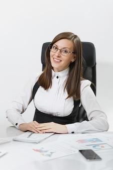 机に座って、ライトオフィスでドキュメントとモダンなモニターとコンピューターで作業しているスーツとメガネの美しい笑顔の茶色の髪のビジネス女性
