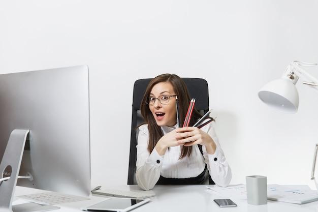 Красивая улыбающаяся каштановая деловая женщина в костюме сидит за столом с карандашами, работая за компьютером с современным монитором с документами в легком офисе
