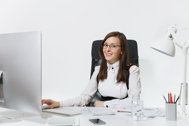 Beautiful smiling brown-hair business woman in suit and glasses sitting at the desk with glass of pure water, working at computer with modern monitor with documents in light office