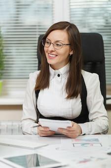 Bella sorridente donna d'affari dai capelli castani in giacca e occhiali seduto alla scrivania con tablet, lavorando al computer con documenti in ufficio leggero, scrivendo con informazioni a matita sul taccuino