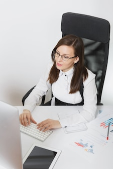 Beautiful smiling brown-hair business woman in suit and glasses sitting at the desk, working at computer with contemporary monitor with documents in light office, hands on keyboard