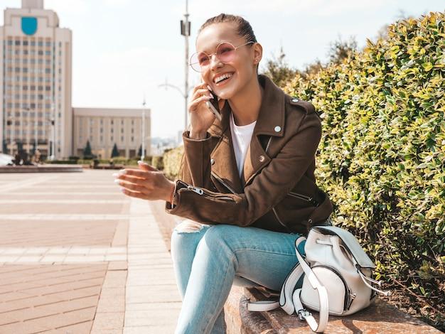 夏の流行に敏感なジャケットとジーンズの服に身を包んだ美しい笑顔ブルネットモデル通りのベンチに座っているトレンディな女の子電話で話す面白いと肯定的な女性