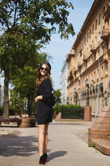 Beautiful and smiling brunette model girl with the trendy backpack in a stylish black dress and in fashionable sunglasses walking by the spring city street