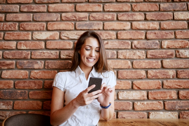Beautiful smiling brunette sitting at coffee shop and using smart phone. in background brick wall.