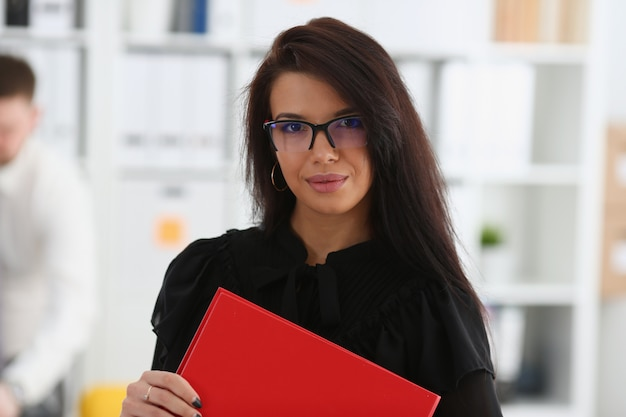 Beautiful smiling brunette woman hold in arms red binder