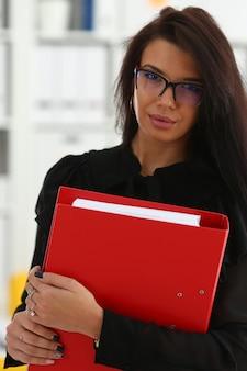 Красивая улыбающаяся брюнетка женщина держит в руках красный переплет