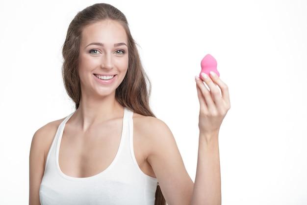 白い背景で隔離の美容ブレンダーを保持している美しい笑顔のブルネットの女性