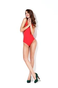 白い壁に赤い水着とハイヒールで美しい笑顔のブルネットの女性