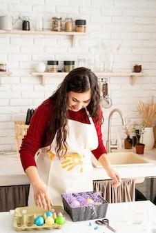 カラフルなイースターエッグを飾る赤いセーターと白いエプロンの美しい笑顔のブルネットの女性