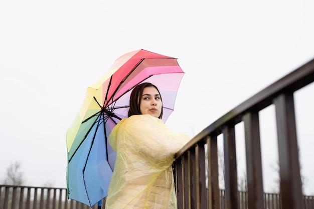 黄色いレインコートを着た美しい笑顔のブルネットの女性が、雨の中で虹の傘を持ち、よそ見。コピースペース