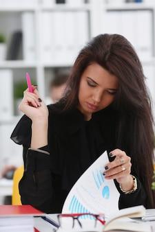 Красивая улыбающаяся брюнетка женщина сидит за столом, держа в руке документы портрета коллег в фоновом режиме.