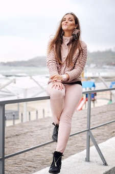 町のビーチの前のフェンスに座っている美しい笑顔のブルネットの女性