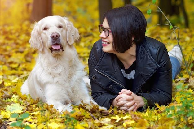 Красивая усмехаясь женщина брюнет с золотистым ретривером в осеннем парке.