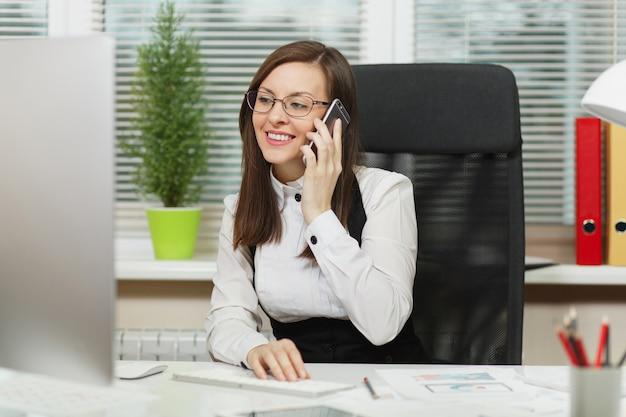 デスクに座って、明るいオフィスでドキュメントを使用して現代のコンピューターで作業し、携帯電話で話し、楽しい会話を行うスーツと眼鏡の美しい笑顔のビジネス女性