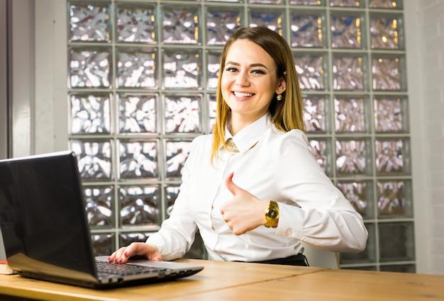 彼女のラップトップの横に親指を現して美しい笑顔ビジネス女性