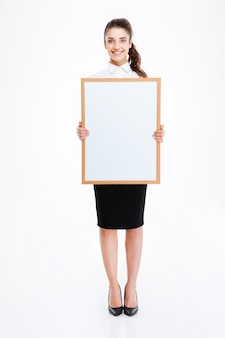 Beautiful smiling businesswoman holding blank board over white wall