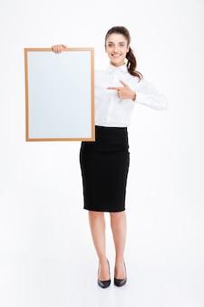 Красивая улыбающаяся деловая женщина, указывая пальцем на пустую доску над белой стеной