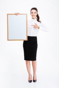 Beautiful smiling businesswoman pointing finger at blank board over white wall