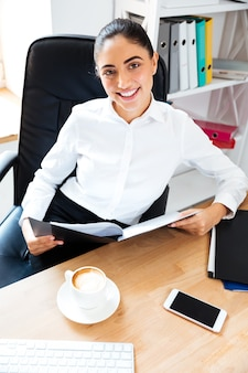 オフィスの机に座って正面を見ながらドキュメントを読んで美しい笑顔の実業家
