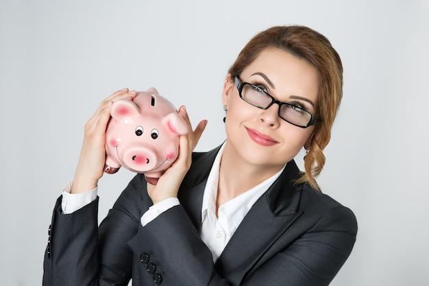 金額をチェックする貯金箱を振って美しい笑顔の実業家。銀行、保険、お金の資本の概念。