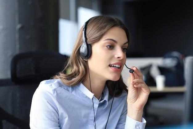 Красивый улыбающийся работник call-центра в наушниках работает в современном офисе.