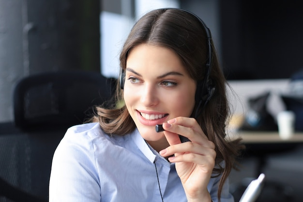 헤드폰을 끼고 웃고 있는 아름다운 콜센터 직원이 현대적인 사무실에서 일하고 있습니다.