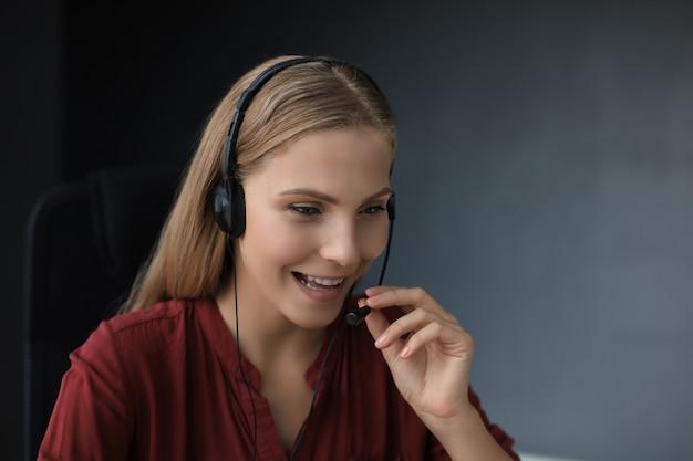 헤드폰을 끼고 웃고 있는 아름다운 콜센터 직원이 회색 배경에서 격리되어 일하고 있습니다.
