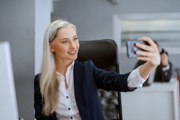 Beautiful smiling caucasian blonde woman sitting in office and looking at herself in smart phone reflection.