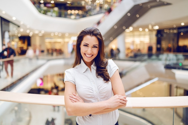 Beautiful smiling caucasian brunette in shirt standing in shopping mall with arms crossed.