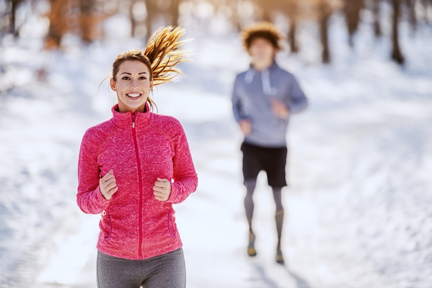 Beautiful smiling caucasian brunette in sportswear running in nature. in background her friend trying to catch up her. wintertime, outdoor fitness concept.
