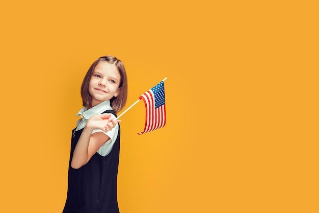 노란색 배경 미국 국기에 미국 국기를 들고 아름 다운 미소 백인 여학생